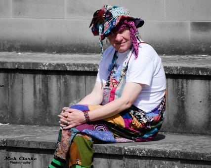 Colourfully dressed man sitting outside Leeds Central Library